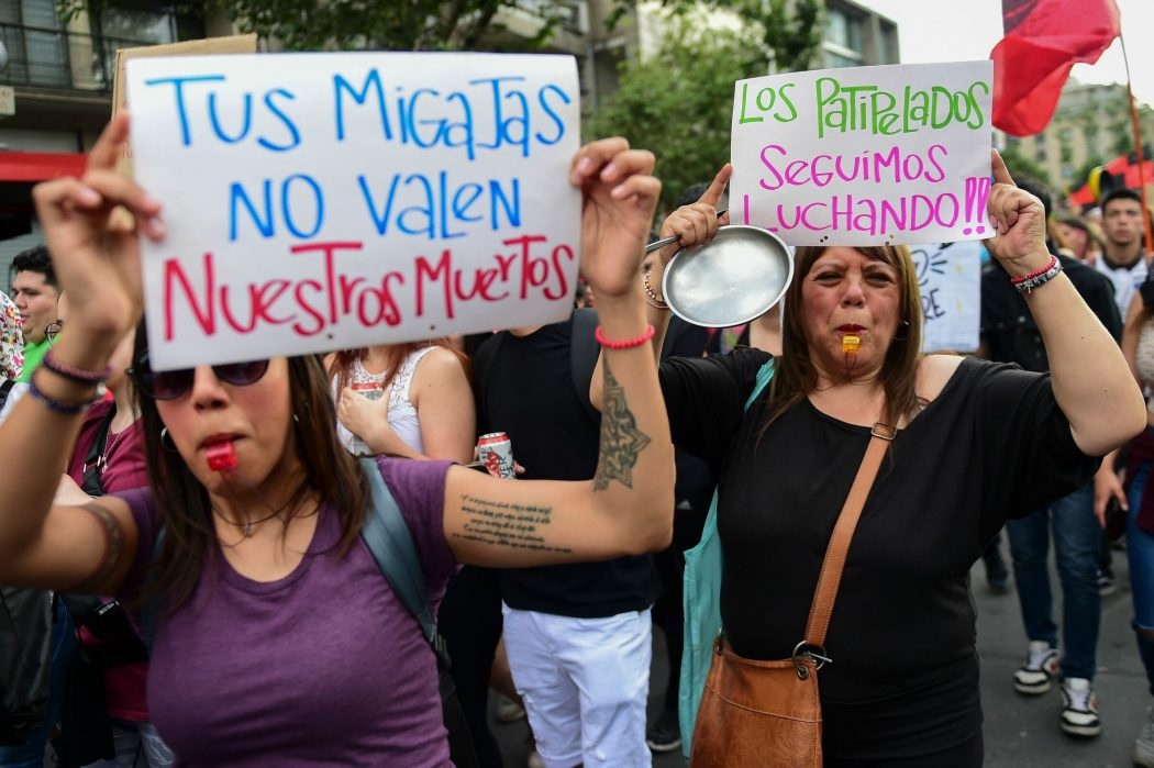 "People demonstrate with signs reading ""Your crumbs are not worth our dead"" and ""The poor keep fighting"" in Santiago, on October 25, 2019, a week after violence protests started. – Demonstrations against a hike in metro ticket prices in Chile's capital exploded into violence on October 18, unleashing widening protests over living costs and social inequality. (Photo by Martin BERNETTI / AFP)"