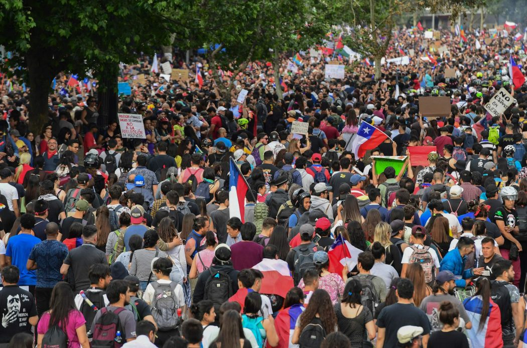 People demonstrate in Santiago, on October 25, 2019, a week after violence protests started. – Demonstrations against a hike in metro ticket prices in Chile's capital exploded into violence on October 18, unleashing widening protests over living costs and social inequality. (Photo by Martin BERNETTI / AFP)