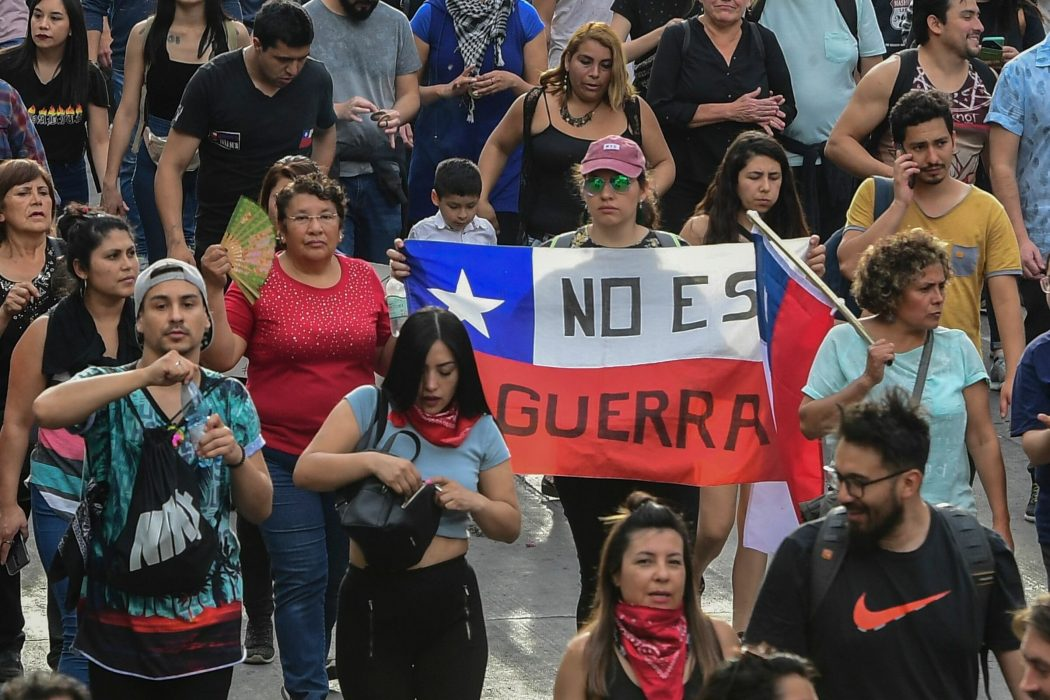 "People demonstrate with a Chilean national flag reaidng ""It is not war"" in Santiago, on October 25, 2019, a week after violence protests started. – Demonstrations against a hike in metro ticket prices in Chile's capital exploded into violence on October 18, unleashing widening protests over living costs and social inequality. (Photo by Martin BERNETTI / AFP)"