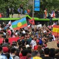 "People demonstrate with a Mapuche indigenous flag and signs reading ""Corrupts to jail"" and ""National referendum. Chile woke up"" in Santiago, on October 25, 2019, a week after violence protests started. – Demonstrations against a hike in metro ticket prices in Chile's capital exploded into violence on October 18, unleashing widening protests over living costs and social inequality. (Photo by Martin BERNETTI / AFP)"