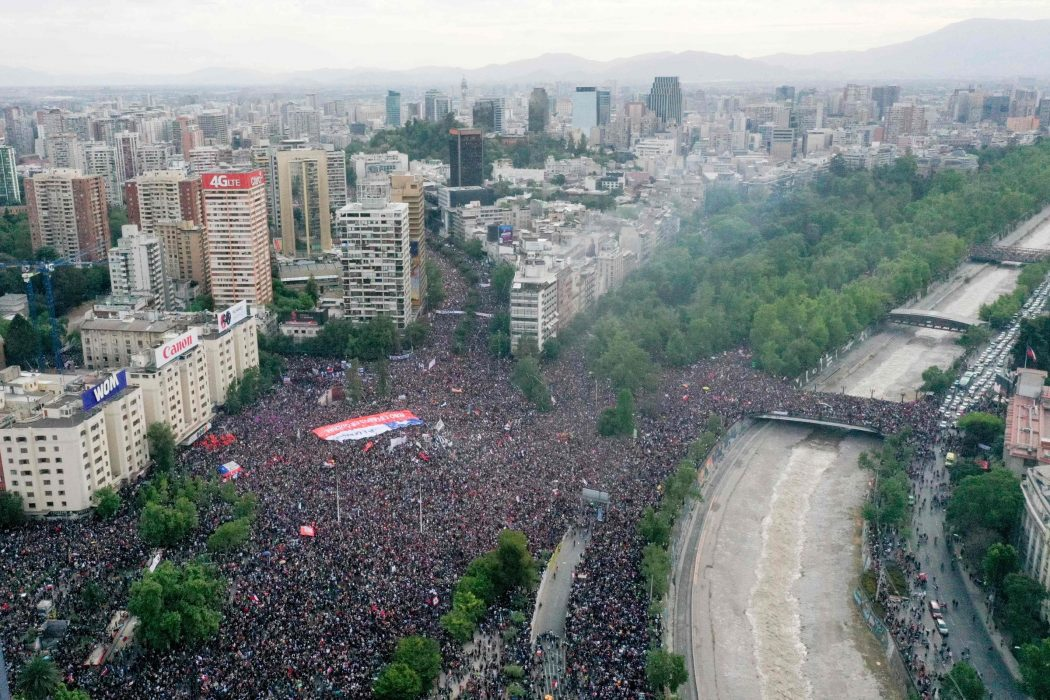 In this aerial view thousands of people protest in Santiago, on October 25, 2019, a week after violence protests started. – Demonstrations against a hike in metro ticket prices in Chile's capital exploded into violence on October 18, unleashing widening protests over living costs and social inequality. (Photo by PEDRO UGARTE / AFP)
