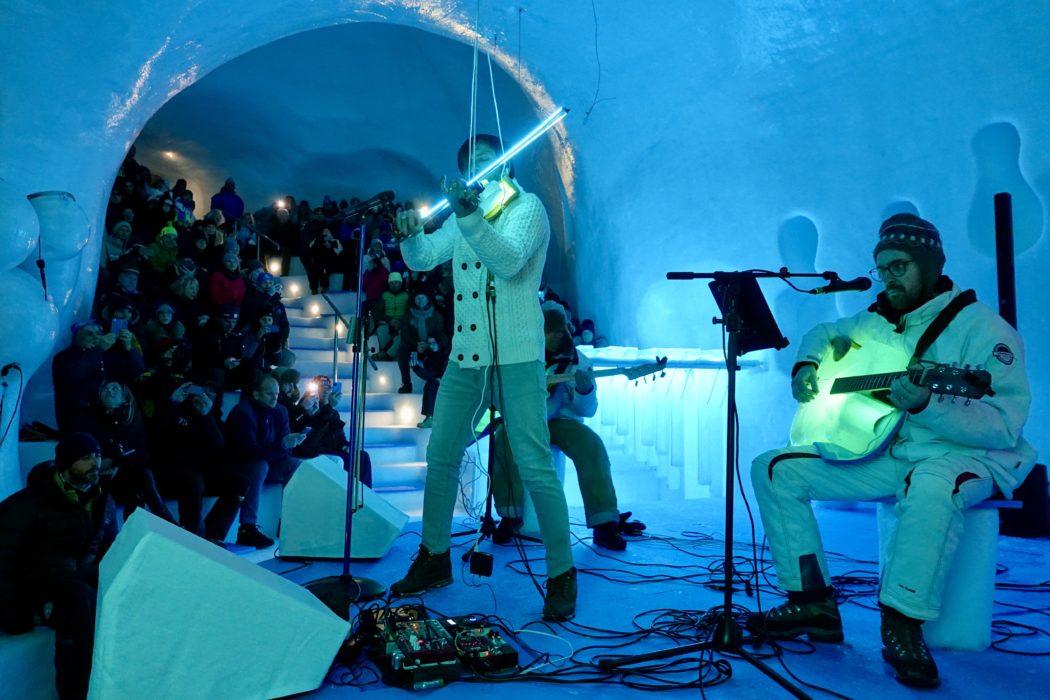 Il violinista Andrea costa con uno strumento di ghiaccio e archetto luminoso.