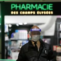 A security officer wearing a face shield and gloves stands in front a drugstore Monday, May 11, 2020 in Paris. The French began leaving their homes and apartments for the first time in two months without permission slips as the country cautiously lifted its lockdown. Clothing stores, coiffures and other businesses large and small were reopening on Monday _ with strict precautions to keep the coronavirus at bay. (AP Photo/Francois Mori)