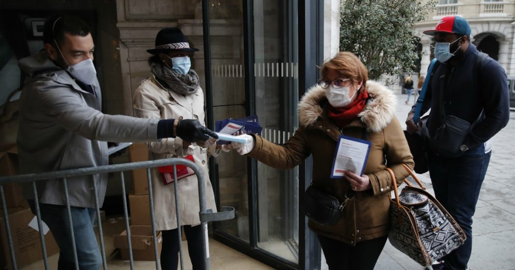 Volunteers distribute the compulsory face masks in public transports to commuters at the Saint Lazare train station Monday, May 11, 2020 in Paris. France is begin to reopen Monday after two months of virus confinement measures. Shops, hair salons and some other businesses are reopening Monday and French citizens no longer need a special permission form to leave the house. (AP Photo/Francois Mori)