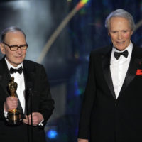 "FILE – In this Feb. 25, 2007 file photo, Italian composer Ennio Morricone, left, accepts an honorary Oscar for his contributions to the art of film music as director Clint Eastwood looks on during the 79th Academy Awards telecast in Los Angeles. Morricone, who created the coyote-howl theme for the iconic Spaghetti Western ""The Good, the Bad and the Ugly"" and the soundtracks such classic Hollywood gangster movies as ""The Untouchables,"" died Monday, July 6, 2020 in a Rome hospital at the age of 91. (AP Photo/Mark J. Terrill, file)"