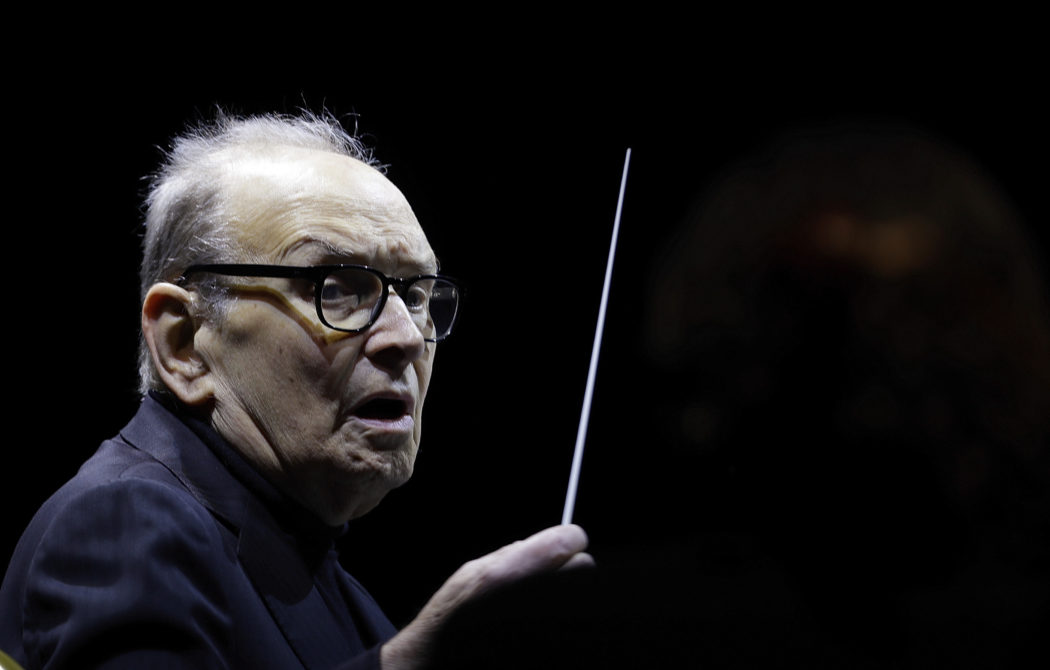 "FILE – In this file photo dated Tuesday, March 6, 2018, Italian composer Ennio Morricone directs an ensemble during a concert of his ""60 Year Of Music World Tour"", in Milan, Italy. Morricone, who created the coyote-howl theme for the iconic Spaghetti Western ""The Good, the Bad and the Ugly"" and the soundtracks such classic Hollywood gangster movies as ""The Untouchables,"" died Monday, July 6, 2020 in a Rome hospital at the age of 91. (AP Photo/Luca Bruno, file)"