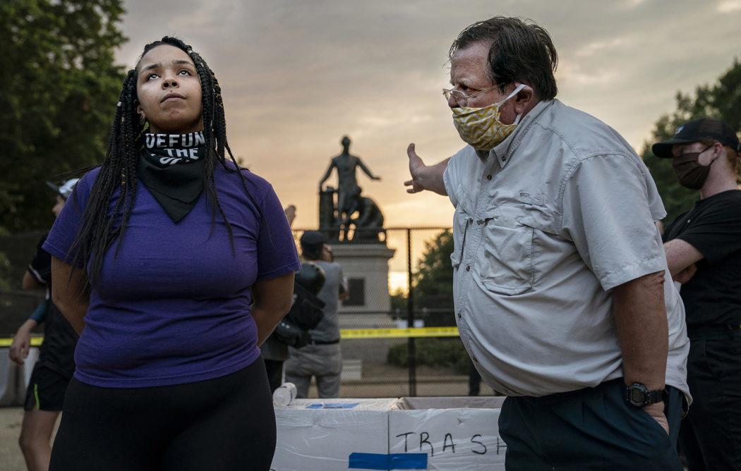 """Per la categoria """"Spot News"""" il primo premio è andato a Evelyn Hockstein: nella foto una manifestante chiede la rimozione dell'Emancipation Memorial (che raffigura il presidente Abraham Lincoln mentre libera uno schiavo afroamericano, inginocchiato e incatenato ai suoi piedi), mentre discute con un uomo che desidera mantenerlo"""