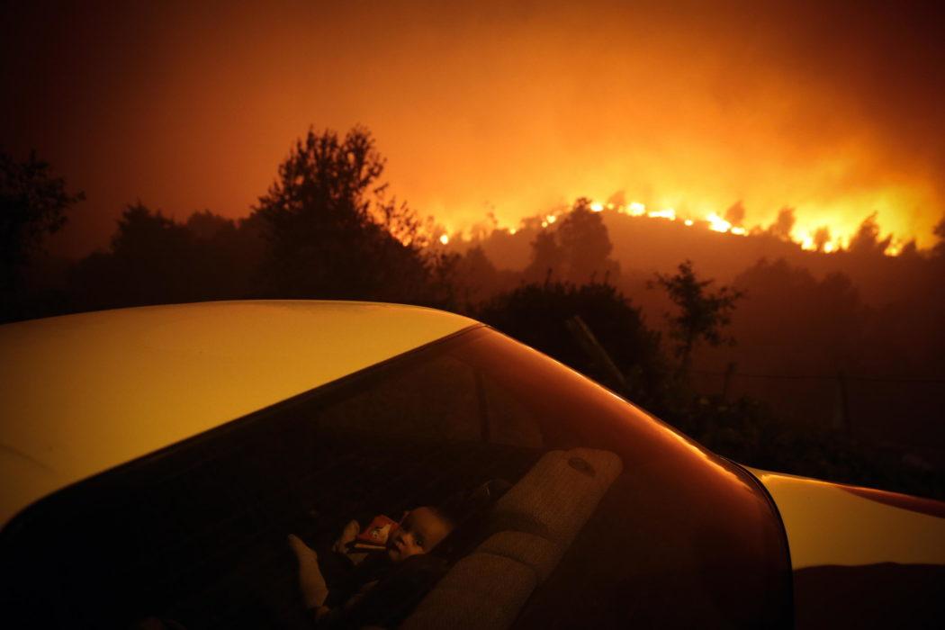 """Al terzo posto della sezione """"Spot News"""" la foto di Nuno André Ferreira che ritrae un bambino in un'auto durante un incendio a Oliveira de Frades, in Portogallo"""