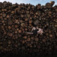 """Nella sezione """"Sport"""" si è aggiudicato la vittoria Adam Pretty: la foto ritrae un uomo che si arrampica su una catasta di tronchi mentre si allena per il """"boulder"""", una particolare arrampicata su piccole formazioni rocciose e massi senza corde o imbracature"""