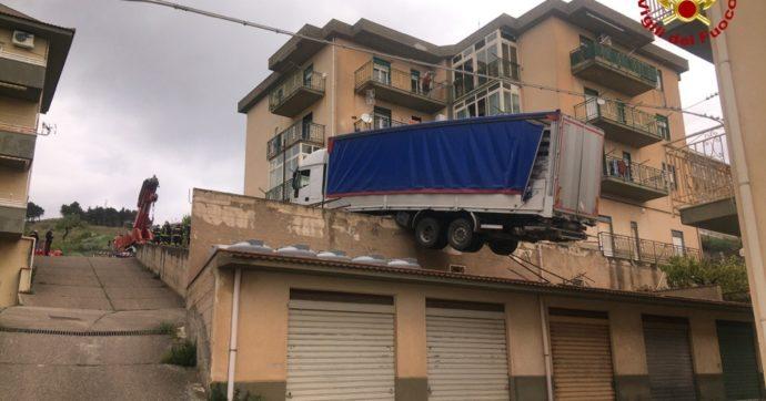Il camion in bilico sul tetto dei garage: la foto. L'intervento dei vigili del fuoco
