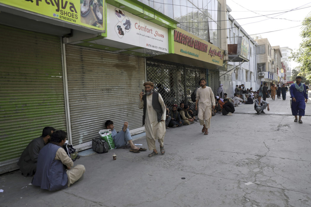 Afghans line a mostly shuttered market for hours to try to withdraw money from a nearby bank, in Kabul, Afghanistan, Sunday, Aug. 15, 2021. Officials say Taliban fighters have entered Kabul and are seeking the unconditional surrender of the central government. (AP Photo/Rahmat Gul)