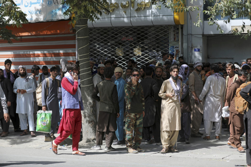 Afghans wait in long lines for hours to withdraw money, in front of Kabul Bank, in Kabul, Afghanistan, Sunday, Aug. 15, 2021. Officials say Taliban fighters have entered Kabul and are seeking the unconditional surrender of the central government. (AP Photo/Rahmat Gul)